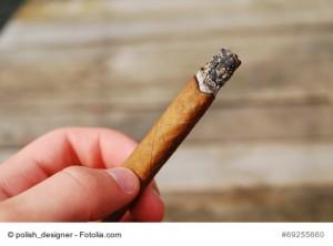 palenie cygara, cygaro w rce - w tle deski, drewno